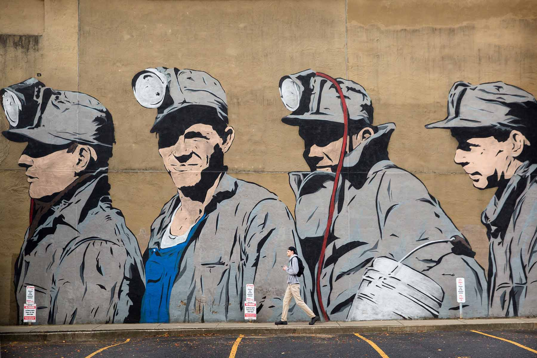Photograph of a pedestrian passing ther coal mine mural in Uptown district or Athens, Ohio on Oct. 27, 2016. The mural was created by Chris Stain with the help of Ohio University Fine Arts students