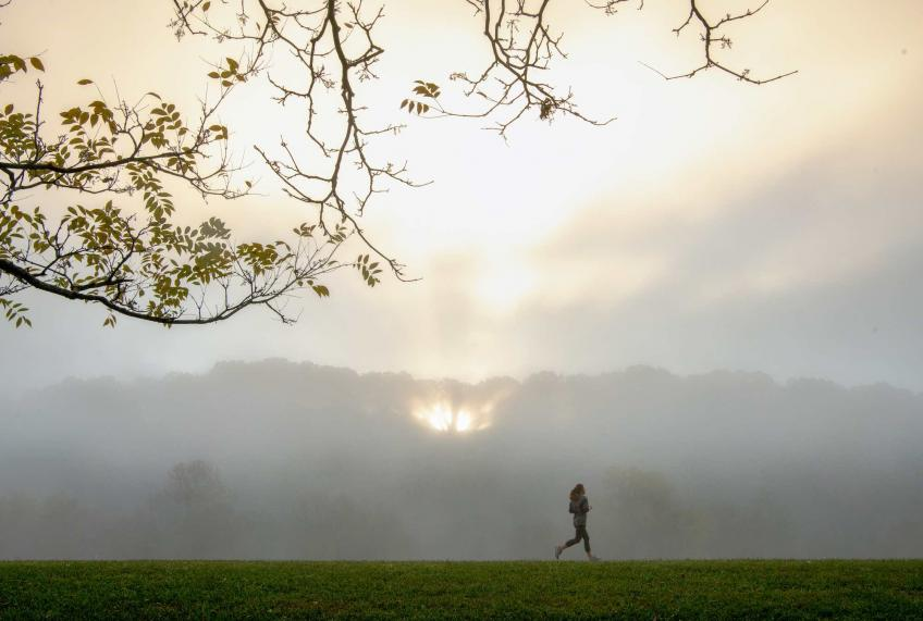 A lone runner on the Athens bike path amongst a foggy sunrise