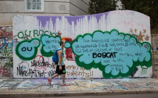 A student walks by in front of the graffiti wall, which is covered in different bright designs