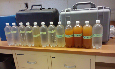 Water collected from the headwaters above the doser (far right). The orange water is from the sacrifice zone, followed by clear water 11 to 12 miles downstream.