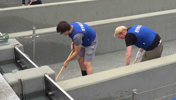 From left, in the foreground inside fish chute: OHIO Sophomore Nick Farris and Senior Ben Piper help to scrub clean the concrete fish-egg chutes at a local fish hatchery used to dispense fertilized salmon roe into a nearby river as part of the OHIO-IPU Ts