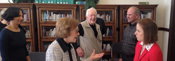 History graduate student Eryn Kane (in red) talks with Rosalynn Carter, as President Carter looks on.