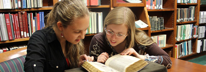 From left, Julianna Coleman, an Honors Tutorial College student double majoring in English and Spanish, and Devon Swanson '18, a double major in English and Theater, with a minor in Spanish, examining a 13-century illuminated Bible in Alden Library archives.