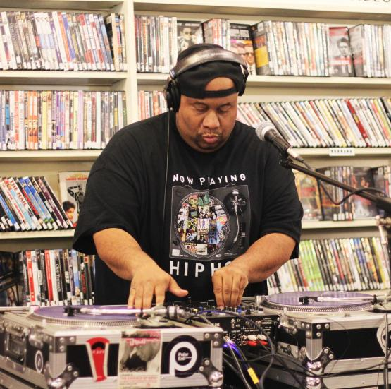 Jason Rawls DJ's in front of shelves full of movies.