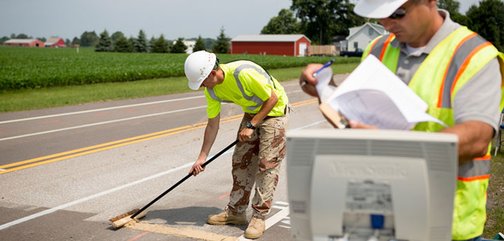 On a two-lane road next to a farm, a worker uses a push broom to spread a mud-like substance on the road surface while a second worker consults some papers