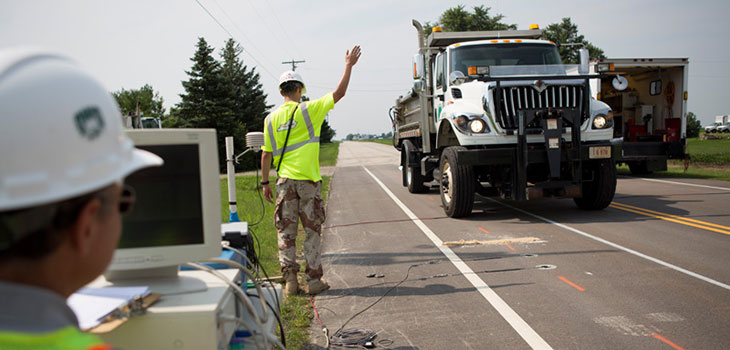 Road worker directs a dump truck on a rural two-lane highway while another worker stands next to a computer connected to cables extending onto the road