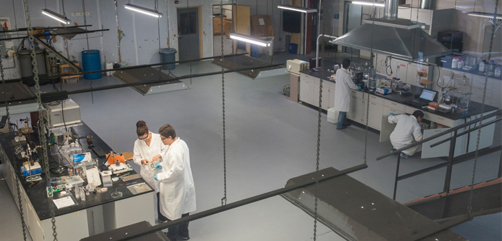 Lab in which researchers are working with equipment at two tables several meters apart