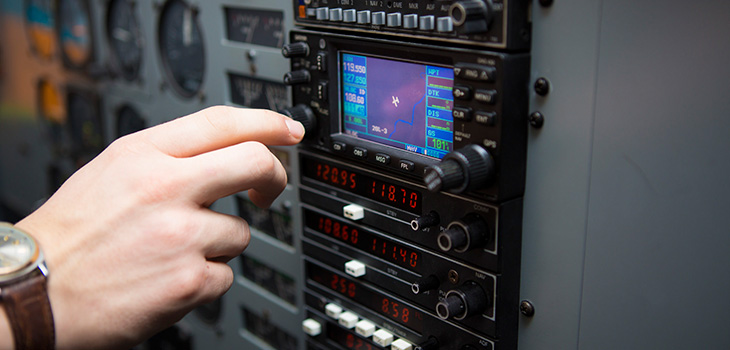 Hand reaching toward a control panel with a small screen showing an airplane's position