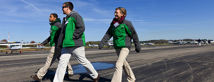 Three young adults in matching jackets walking down an airport runway