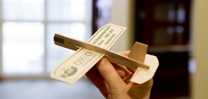 Hand holding toy balsa wood airplane with Ohio University logo on the wing