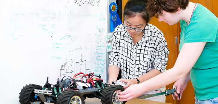 two students working on a remote control car
