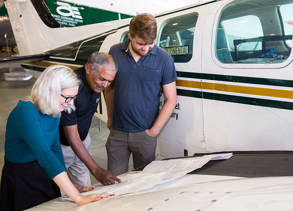 Three researchers, one female and two males, look over plans in an airport hangar