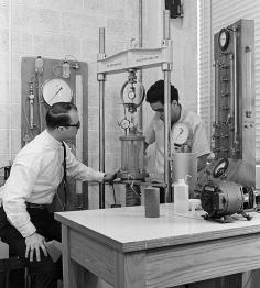 Nostalgic black and white image of past civil engineers working with lab equipment.