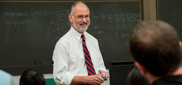A professor smiling at his class.