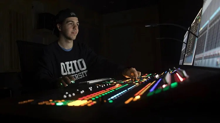 Christopher Pentecost, BSC '19, is seen inside Ohio University's Schoonover Center 448, the MDIA Sound Post-Production and Listening Lab, where he spent countless hours as an undergraduate mastering the skill of creating and editing the mosaic of sounds that bring stories to life.