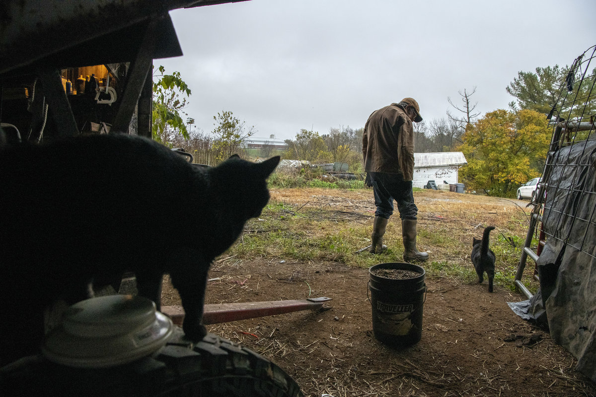 Cattle farmer Lowell Clifford leaves his barn on a stormy morning while chatting with his cat, Skinny, as his other barn cat, Fatty, looks on while perched atop a tractor in Cynthiana, Ken., on Oct. 30, 2019.