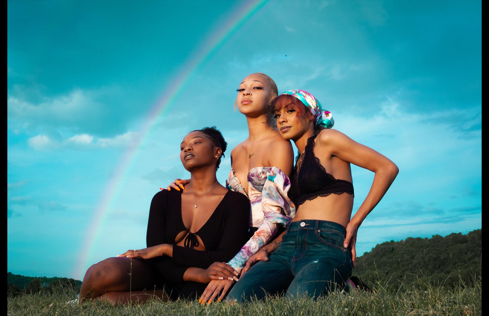 three women in field with rainbow