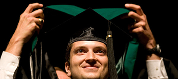 A smiling student during graduation commencement ceremony