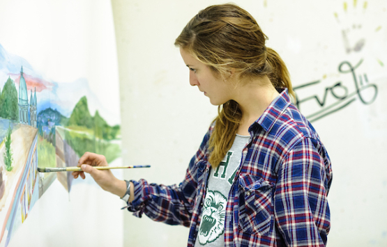Ohio University student working on a painting in an art studio