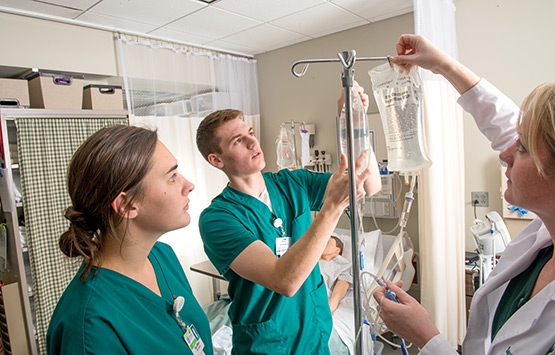 OHIO Nursing students in a real-world setting learning about IV bags.