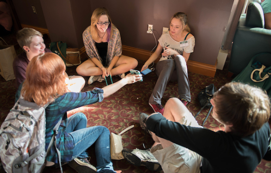 Students sharing with each other while sitting in a circle in a residence hall common area