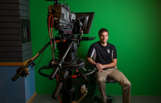 An OHIO alumni poses for a photo with a television camera in front of a green screen