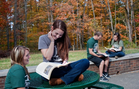 Students reading outside with fall foliage in the background
