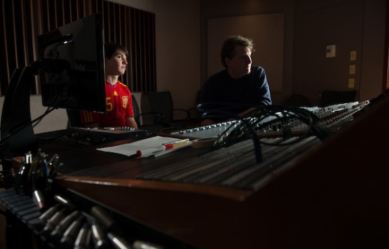 A student intern sits in a studio with a recording engineer