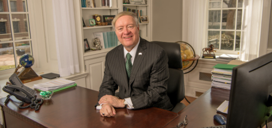 Photo of President Nellis smiling at his desk