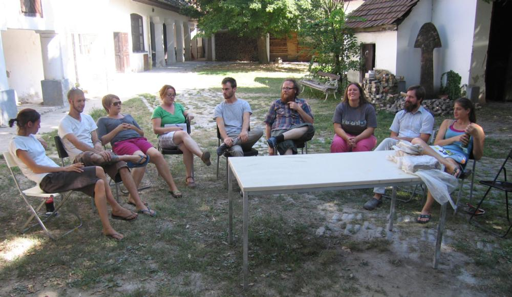 Group of people sitting behind table outside