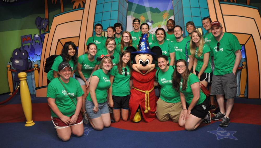 Group of people taking a picture with Mickey Mouse