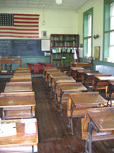 Image of a class room and the flag of the US is seen on the wall.