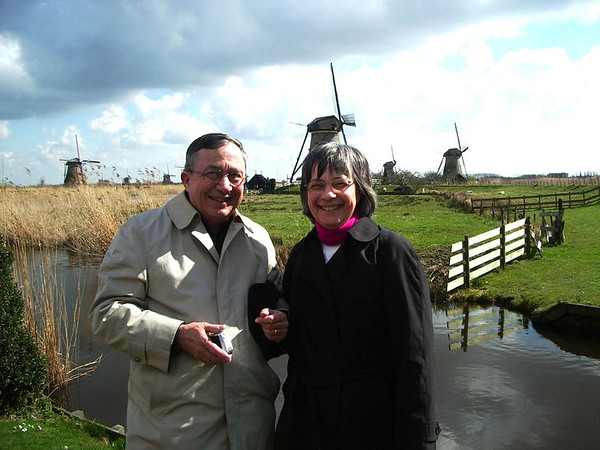 Man and woman standing in front of windmills