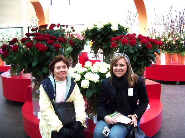 Two women sitting in front of flowers