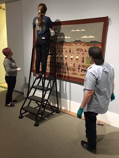 student interns installing exhibition