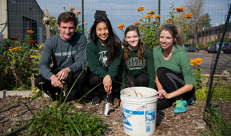 students pose for a group photo while volunteering in a garden
