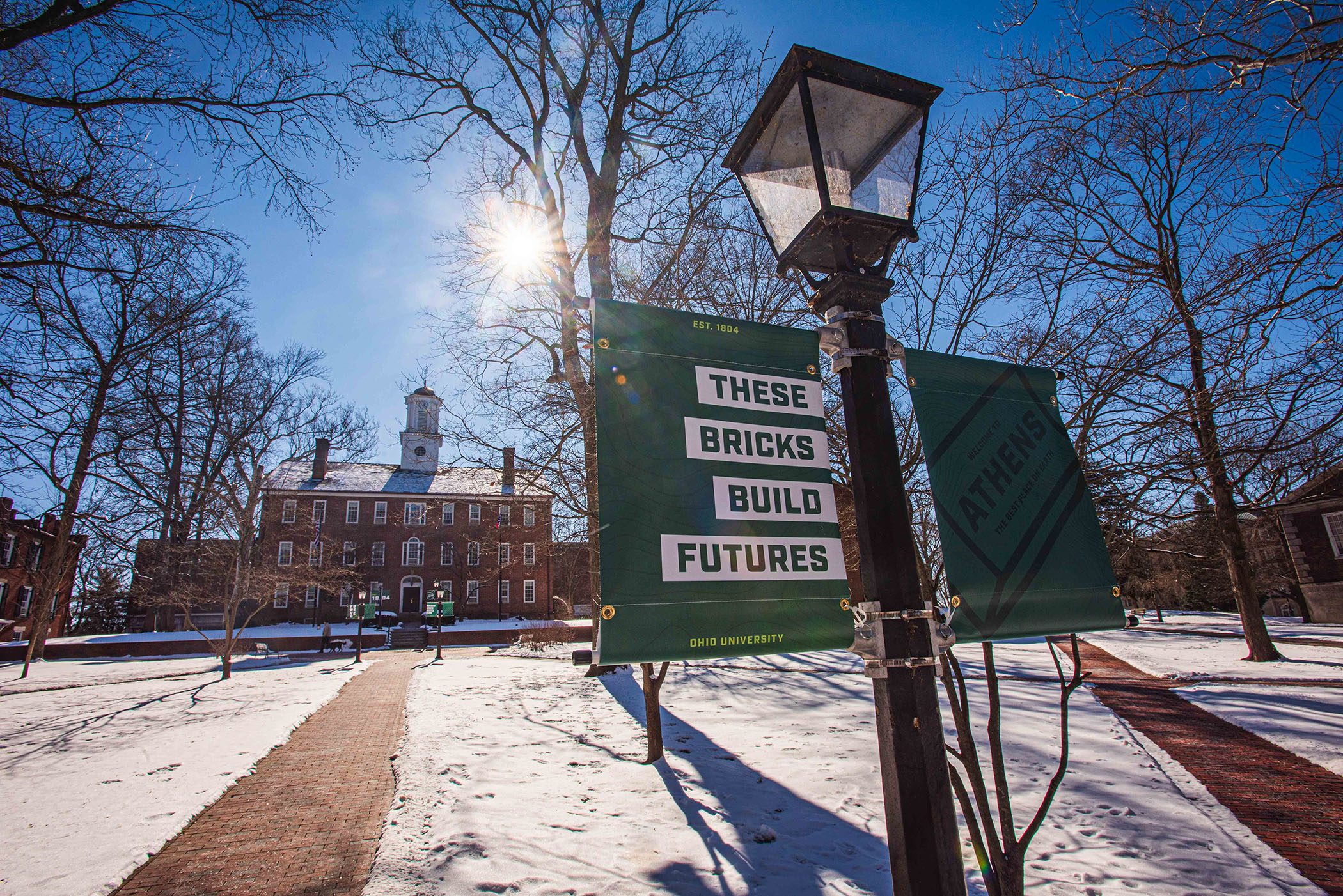 "Snow-covered College Green. Light post banner: ""these bricks build futures."""