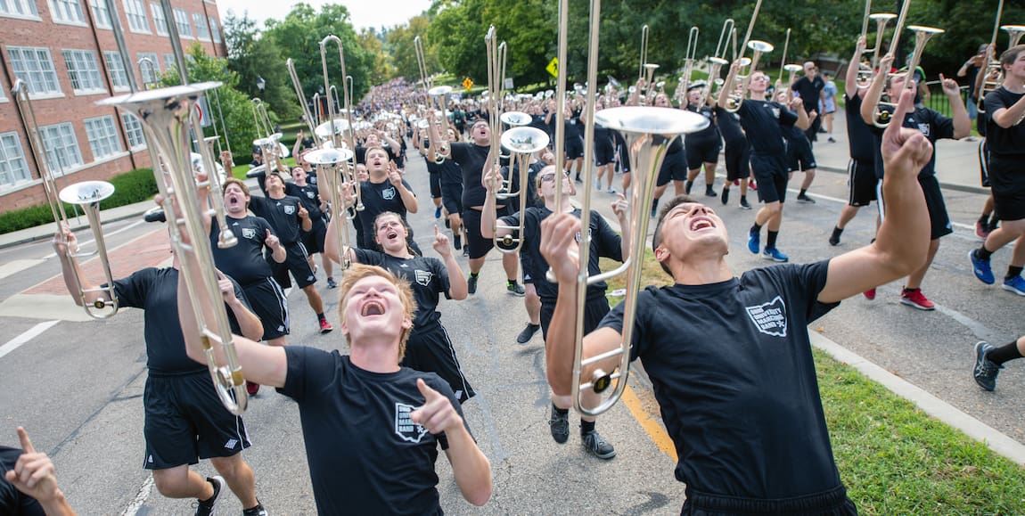 Members of the Ohio University Marching Band shout enthusiastically as they march