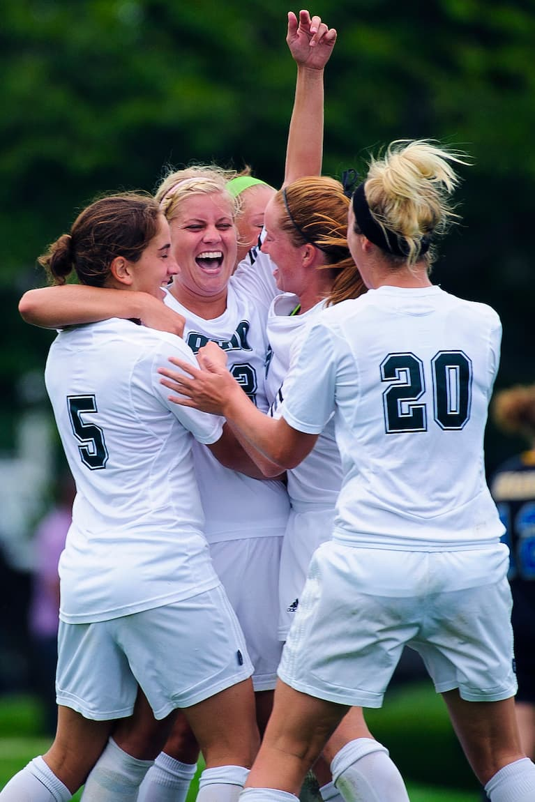 Members of the Ohio University women's soccer team celebrate together on the field