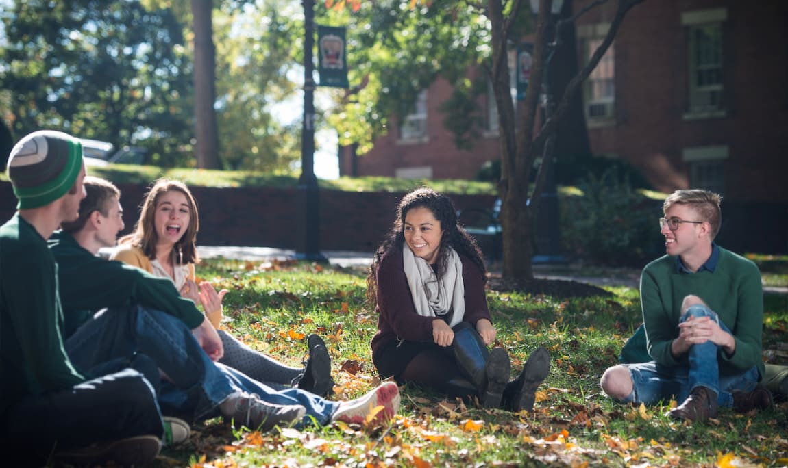 A group of Ohio University students talk and laugh while sitting in the grass together