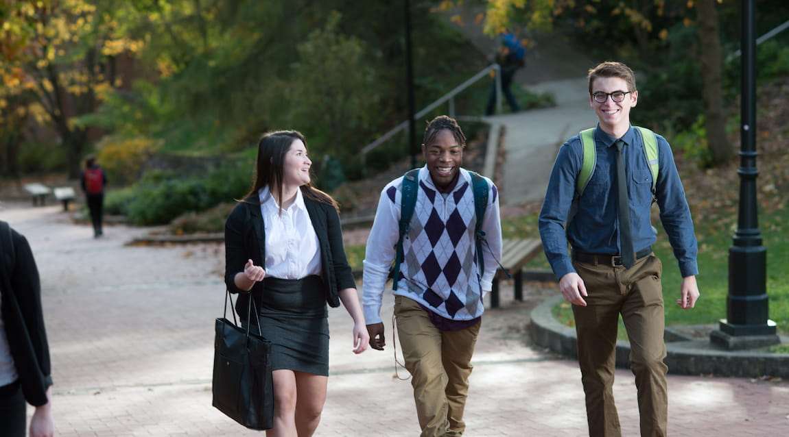 Three students smiling as they walk together on a brick path at Ohio University Athens campus