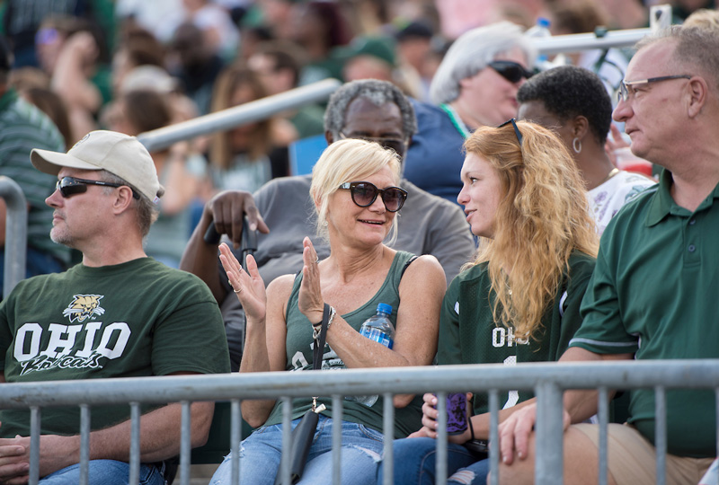 Photo of Ohio University football fans enjoying a game while wearing Bobcat gear