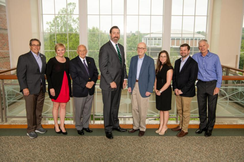 Eight members of the Cutler Scholars Advisory Board pose in front of a window