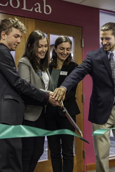 4 students use giant scissors to ceremoniously cut a ribbon in front of CoLab