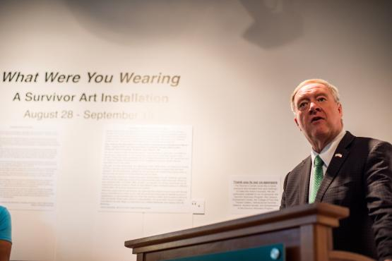 President Nellis speaks in front of the What Were You Wearing exhibit at it's gallery opening.