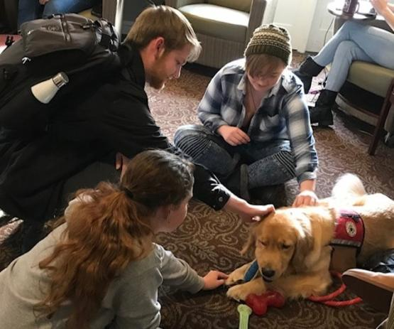 Students pet Chilly the Therapy Dog