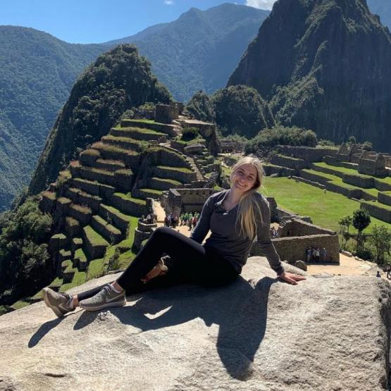 Saylor Evans poses on a rock in front of Machu Picchu