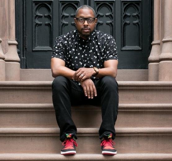 Marcus J. Moore sits on a stoop