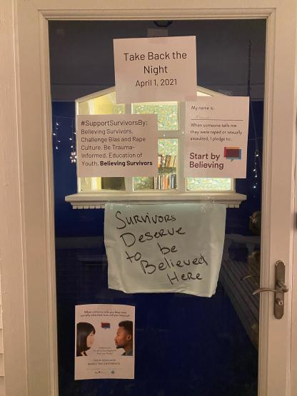 "A door is decorated with messages of support for Take Back the Night, including ""Survivors Deserve to Be Believed Here"", a #StartByBelieving pledge, and a sign that says ""#SupportSurvivorsBy: Believing Survivors, Challenge Bias and Rape Culture, Be Trauma-Informed, Education of Youth, Believing Survivors."" The last ""believing survivors"" is bolded."