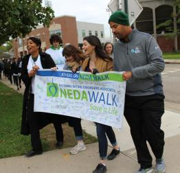 Speakers from the National Eating Disorders Association walk carry the walk banner.